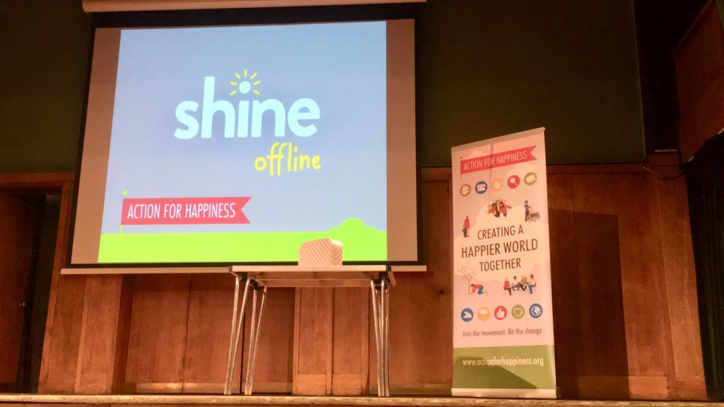 Stage showing Shine Offline logo on screen and Action for Happiness roll up banner